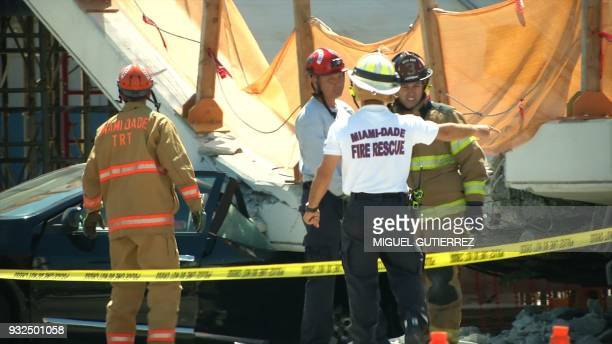 This AFP TV video frame grab shows emergency response workers at a newly installed pedestrian bridge over a sixlane highway in Miami on a college...
