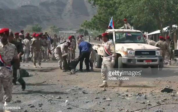 This AFPTV screen grab from a video made on August 1 shows Yemeni security forces carrying a body at the scene of a missile attack on a military camp...