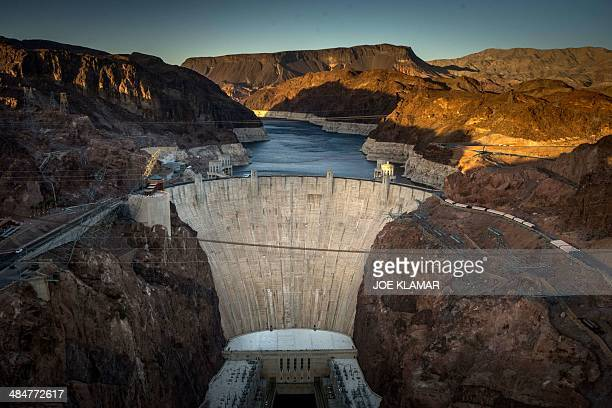This April 13 2014 view shows Hoover Dam a concrete archgravity dam in the Black Canyon of the Colorado River on the border between the US states of...