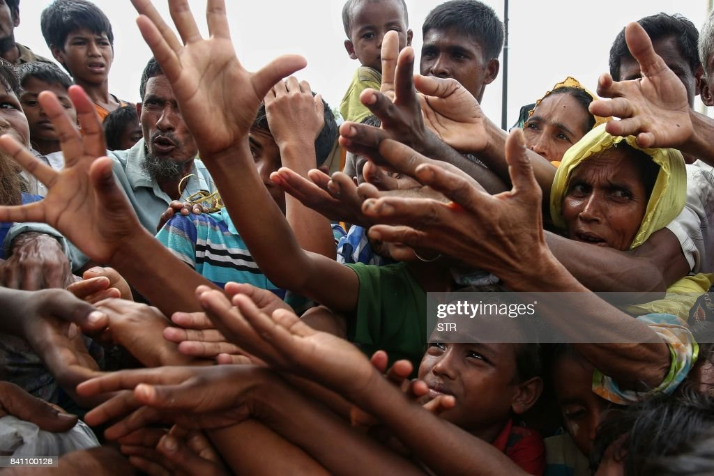 TOPSHOT - This August 30, 2017 photo shows Rohingya refugees reaching for food aid at Kutupalong refugee camp in Ukhiya near the Bangladesh-Myanmar border. The International Organization for Migration said August 30 that at least 18,500 Rohingya had crossed into Bangladesh since fighting erupted in Myanmar's neighbouring Rakhine state six days earlier. PHOTO / STR