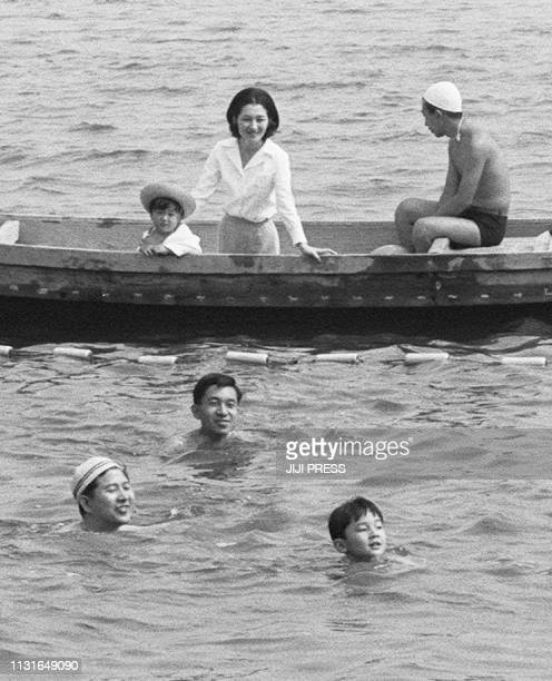 This August 5 1968 picture shows Emperor Akihito Empress Michiko and Prince Akishino watching Crown Prince Naruhito swimming while visiting the Lake...
