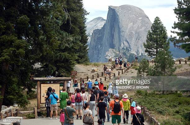 This August 5 2015 photo shows tourists walking out to Glacier Point with a background view of Half Dome at Yosemite National Park A second tourist...