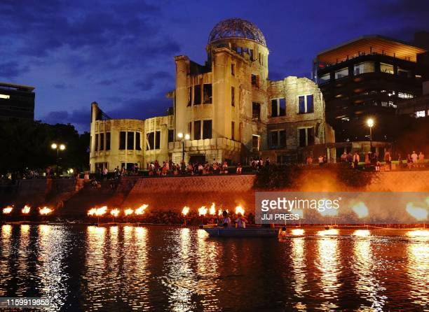 This August 5, 2019 picture shows people standing next to the atomic bomb dome at the Peace Memorial Park in Hiroshima, one day before the 74th...