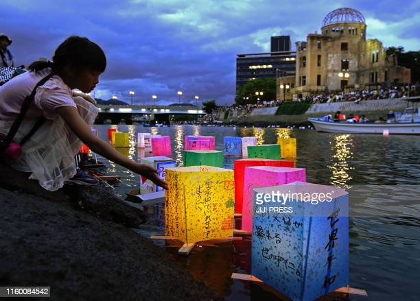 TOPSHOT This August 6 2019 picture shows a girl floating lanterns to mourn atomic bomb victims on the Motoyasu river beside the atomic bomb dome...