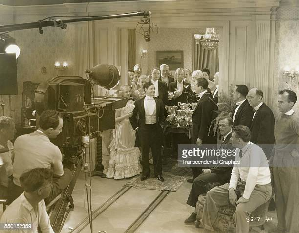 This behindthescenes photograph shows a scene shot in a wealthy mansion Hollywood California circa 1940
