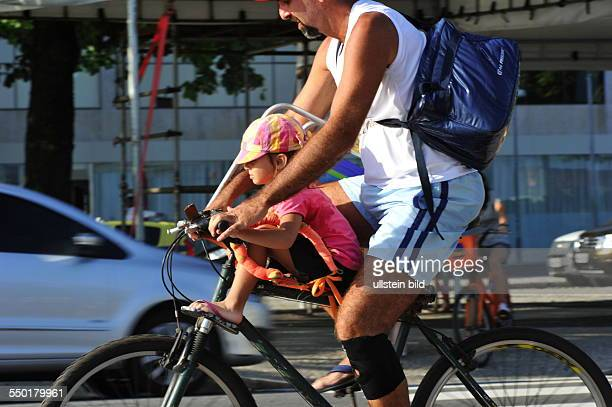 This Brazilian father drives with his son on the bike rack through the city traffic of Rio de Janeiro
