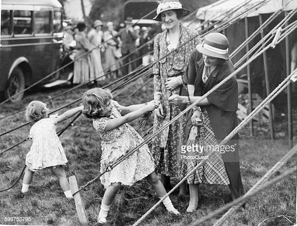 This charming snapshot, taken at the Abergeldie Castle Fete, behind the marquee in which the two little Princesses sold white heather in aid of the...