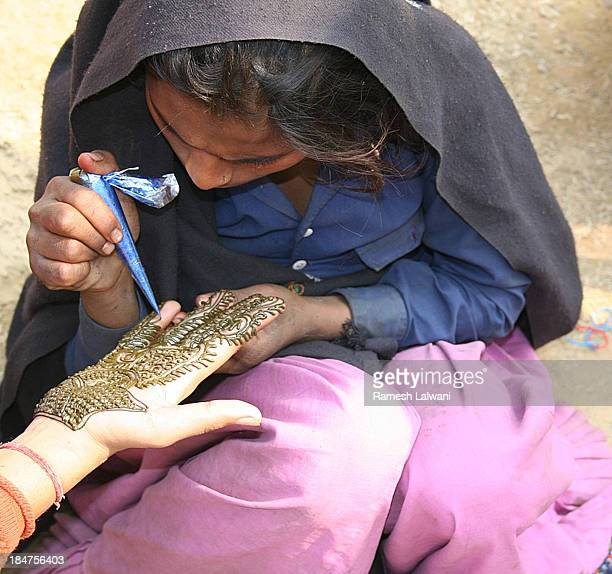 CONTENT] This child is making some money applying henna on girl's handOne can find children in streets doing all sorts of jobs to supplement family...