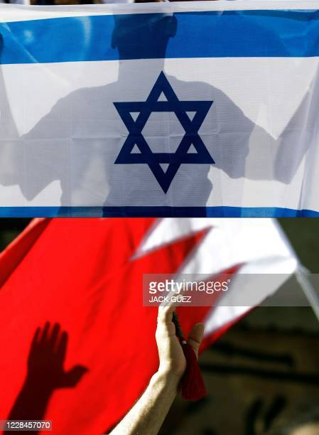 This combination of pictures created on September 11 2020 shows an Israeli man holding his country's national flag on January 24 2017 and a Bahraini...