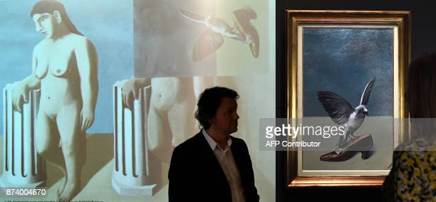 This combination photograph shows a woman looking at 'God is not a Saint' by Belgium artist Rene Magritte which hides under its layers the missing...