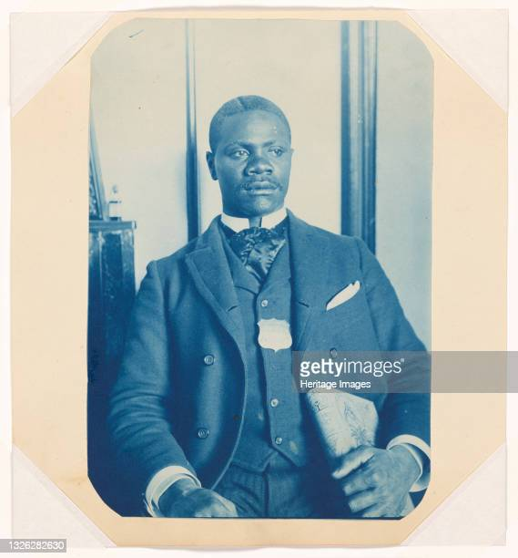 This cyanotype depicts a blue-tinted image of an African-American man wearing a hotel porter badge. The man is seated in front of a window or...
