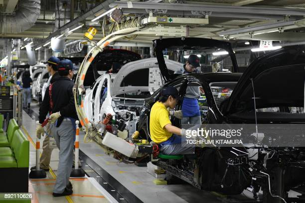This December 8, 2017 picture shows workers assembling fourth generation Toyota Prius cars on the production line at the company's Tsutsumi assembly...