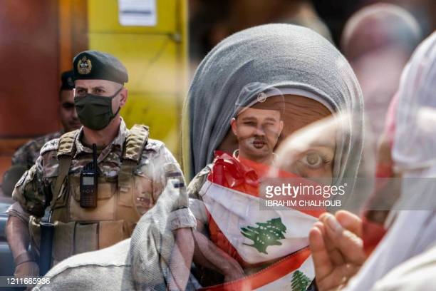 TOPSHOT This double exposure photo taken on May 3 2020 shows a Lebanese protester wearing a Lebanese flag face mask as members of the Lebanese Armed...