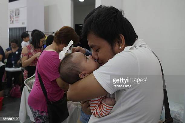 This father kisses his baby Fathers who support mothers who breastfeed They say they able to save more money with breastfeed than buying milk To...