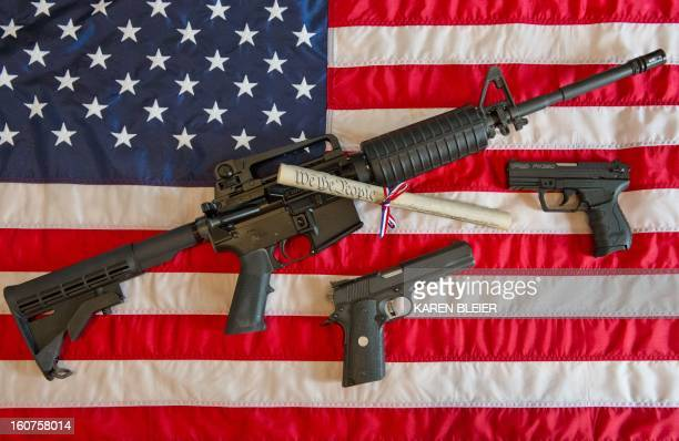 This February 4, 2013 photo illustration in Manassas, Virginia, shows a Colt AR-15 semi-automatic rifle a Colt .45 semi-auto handgun and a Walther...
