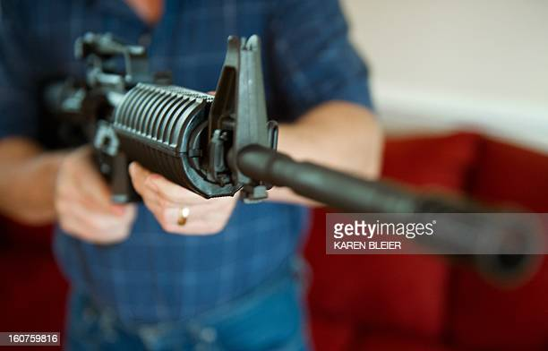 This February 4, 2013 photo illustration in Manassas, Virginia, shows a man holding a Colt AR-15 semi-automatic rifle. US President Barack Obama...