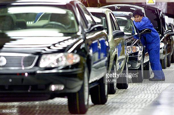 This file photo dated 04 March 2003 shows a worker looking at a side mirror of a car at the assembly line of General Motors Company in Shanghai US...