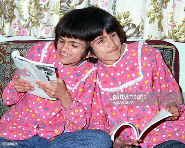 This file photo dated 10 October 1989 shows Iranian sisters Laleh and Ladan Bijani reading in their adoptive father's house in Karaj 46km from Tehran...
