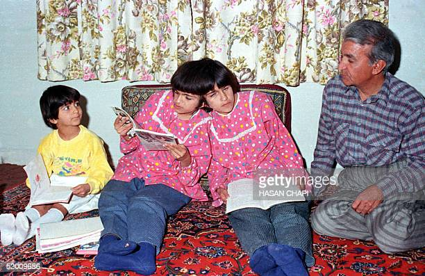 This file photo dated 10 October 1989 shows Iranian sisters Laleh and Ladan Bijani reading as their adoptive father Ali Reza Safaeian and adoptive...