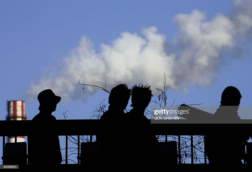 This file photo dated 11 January 2005 shows pedestrians walk across a bridge near a factory's cooling tower billowing gases into the air in Beijing. China, the world's second biggest greenhouse gas emitter after the United States, and a member of the Kyoto Protocol, which took effect worldwide 16 February 2005, has shown its commitment to reducing pollution and switching to renewable energy, but analysts say it still has a long way to go.