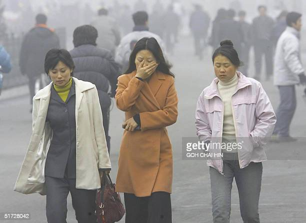 This file photo dated 22 February 2001 shows a woman covering her mouth and nose with her hand as she walks along a street with her friends in...