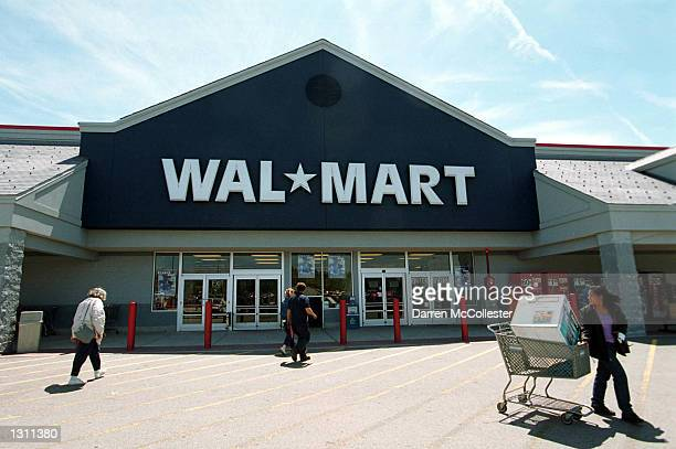 This file photo dated May 25 2001 shows customers entering and exiting a WalMart store in Quincy MA Six women filed a lawsuit against the retail...