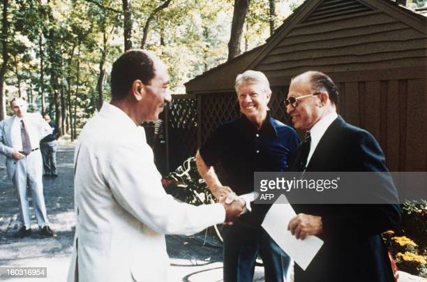 This file photo shows former Egyptian President Anwar alSadat as he shakes hands with former Israeli Premier Menachem Begin as former US President...