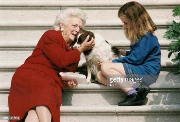 This file photo shows former First Lady Barbara Bush talking to her dog Millie as she and grandaughter Barbara Bush age nine wait for US President...