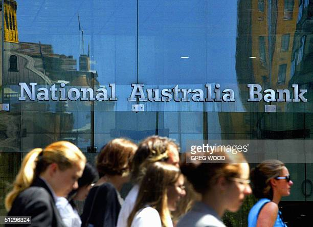 This file photo taken 18 March 2004 shows office workers walking past a National Australia Bank sign in Sydney's central business district It was...