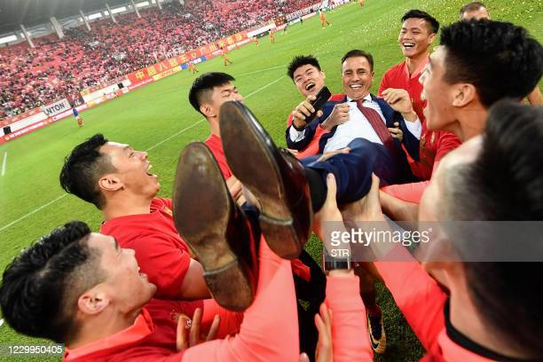 This file photo taken on December 1, 2019 shows players of Guangzhou Evergrande lifting up their head coach Fabio Cannavaro in celebration after...