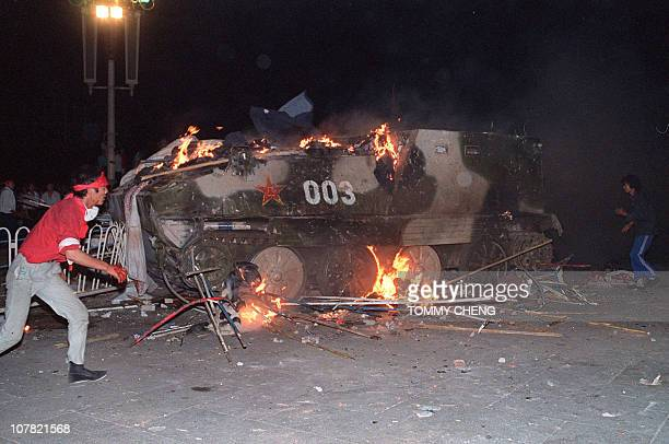 This file photo taken on June 4 1989 shows an armoured personnel carrier in flames as students set it on fire near Tiananmen Square in Beijing...