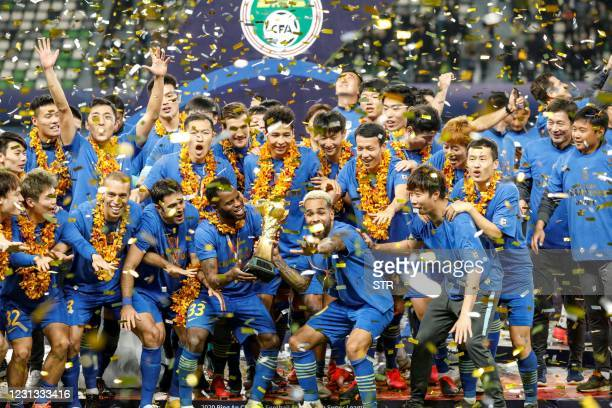 This file photo taken on November 12, 2020 shows Jiangsu Suning players and staff members celebrating after their team defeated Guangzhou Evergrande...