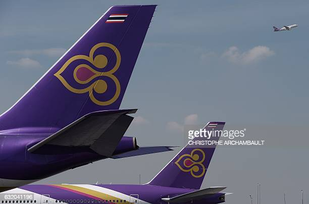 This file photo taken on November 24 2014 shows a Thai Airways aircraft taking off past the tails of two other Thai Airways planes at Bangkok's...