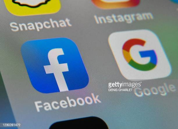 This file photo taken on October 1 shows the logos of mobile apps Facebook and Google displayed on a tablet in Lille, France. - Google and Facebook...