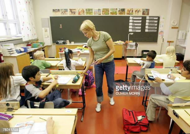 This file picture dated 17 August 2005 shows a teacher giving rulers to children of the second grade in a primary school in Vaasa on their second day...