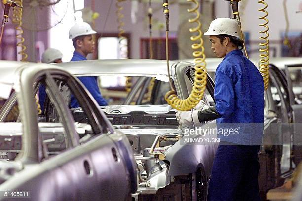 This file picture dated 19 February 2002 shows a worker doing inspection on a car body at the national carmaker's Proton plant near Kuala Lumpur The...