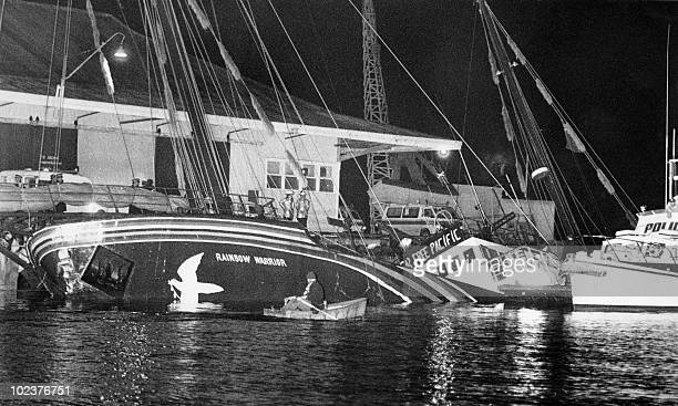 This file picture shows the Greenpeace flagship Rainbow Warrior lying on its side in Auckland harbour on July 10 1985 after being blownup by French...