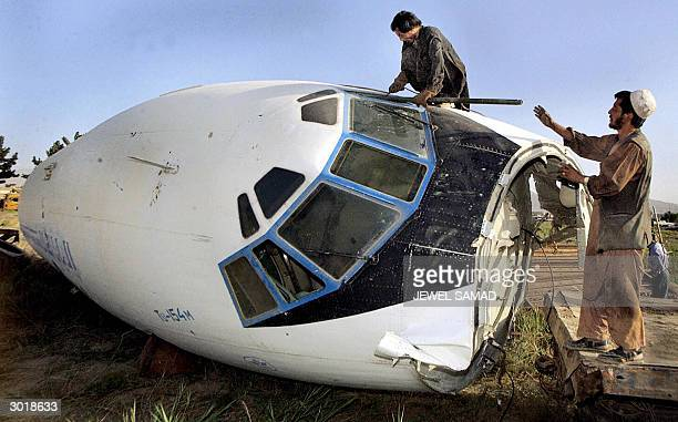 This file picture taken 06 July 2002 shows Afghan workers removing a part of the cockpit of a destroyed plane of a destroyed Afghan national airlines...