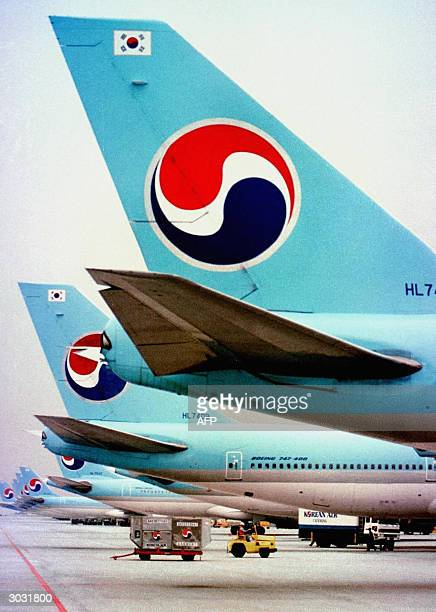 This file picture taken 22 October 2000 shows Korean Air aircraft lined up on the tarmac at Kimpo airport in Seoul South Korea's national flag...