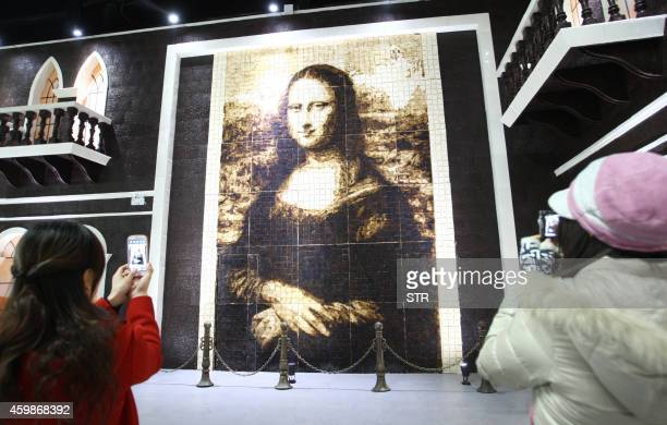 This file picture taken on January 18 2013 shows people taking photos of a chocolatemade Mona Lisa painting at the Chocolate Happy Land in Shanghai...