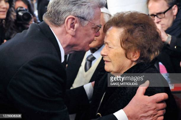 This file picture taken on March 7, 2014 shows ?sther Cohen being kissed by Germany's then president Joachim Gauck during his visit to Ioannina. -...