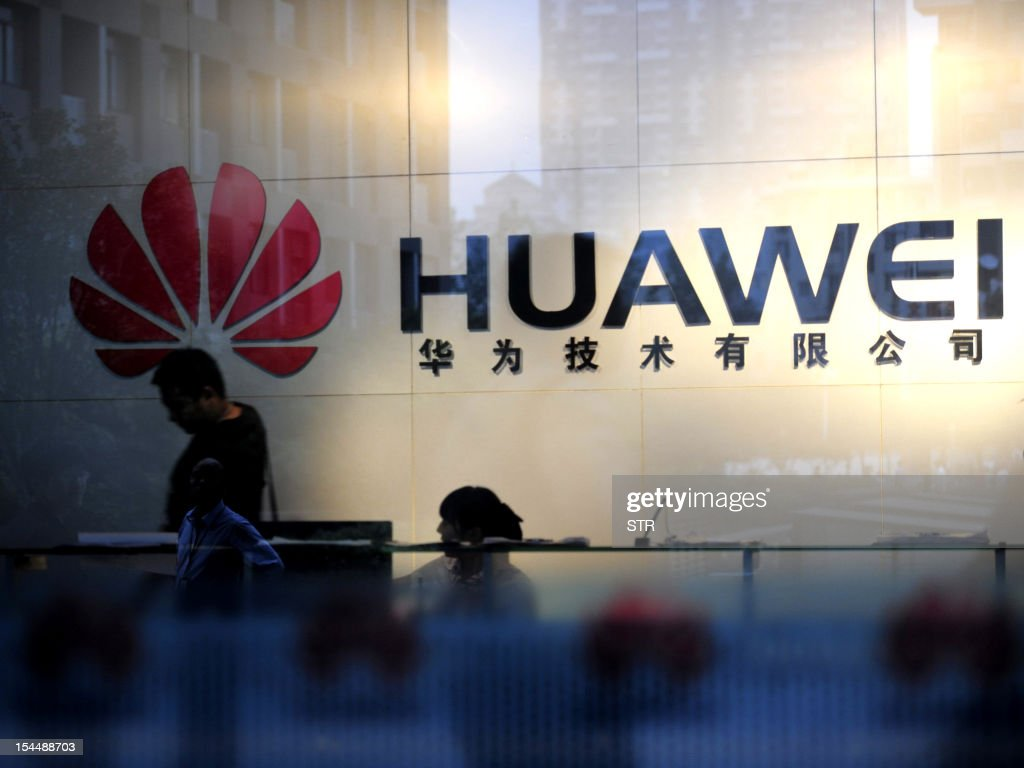 This filephoto dated on October 8, 2012 shows staff and visitors walk pass the lobby at the telecommunications equipment firm Huawei Technologies in Wuhan, central China's Hubei province. US security fears over two China telecom firms have spotlighted Western suspicions Chinese companies are state-influenced, a culture clash analysts say could loom larger as the country's businesses look overseas. CHINA