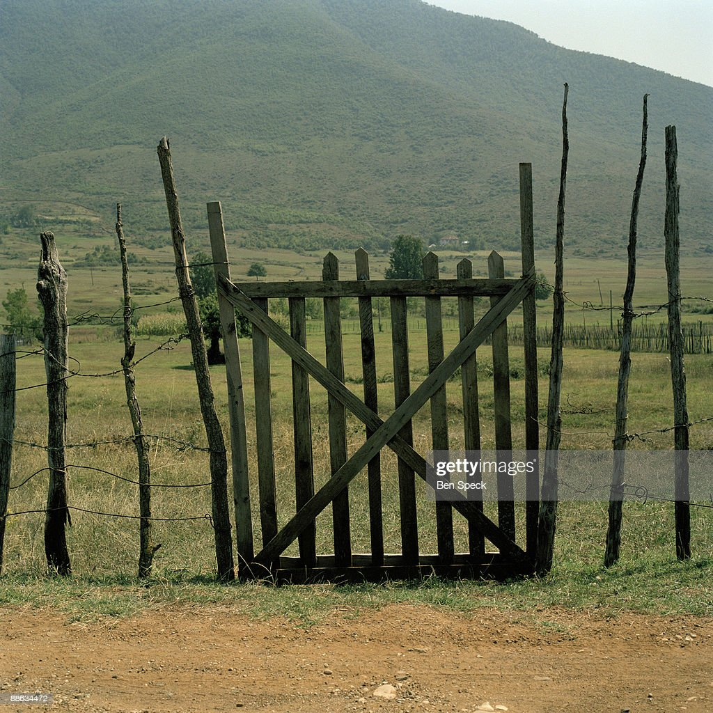 This gate marks the entrance to Haki Shehu's property. She owns a farm and a lot of land. In the patriarchal rural Albanian society the age-old tradition of the Virgjineshe ('sworn virgins') gives women the choice of taking on a male identity in order to enjoy male privileges. Becoming a 'sworn virgin' means to vow lifelong celibacy and to turn into a surrogate son to her father. The reasons for taking the vow are a lack of sufficient men in a family to carry out the men's work, or the lack of a headstrong man to become the head of the family. A woman might also escape an unwanted arranged marriage, without damaging family honour or she might want to be independent to travel and work as she pleases. Often the decision is made by the family head e.g. her father, grandfather or uncle. The girl or woman then acquires a male name, male clothes and a male haircut. With the new status she obtains all the male privileges, such as inheriting property, making decisions within the family and the community, being able to carry weapons, taking part in blood feuds and socializing freely with men. They are completely accepted and addressed as men by other members of their community and often behave more manly than the men. The occurrence of Tobelija is most common in and around Bjesket e Nemuna (The Accursed Mountains) covering the northern regions of Albania and bordering regions of Montenegro and Kosovo.