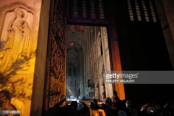TOPSHOT This general view from the entrance shows smoke rising in front of the altar cross at NotreDame Cathedral in Paris on April 15 after a fire...
