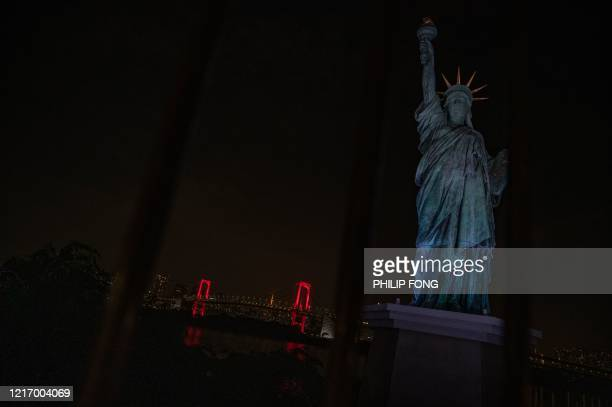 This general view photo shows a replica of the Statue of Liberty and the Rainbow Bridge lited up at night in red after Tokyo government decided to...