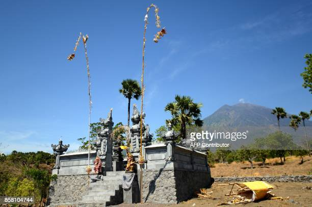 This general view shows a small Balinese temple as Mount Agung volcano looms in the background in the Kubu subdistrict in Karangasem Regency on...