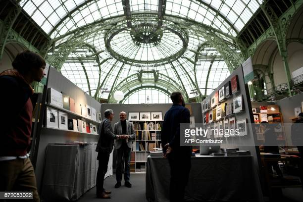 This general view shows exhibitors and visitors as they attend 'Paris Photo' at The Grand Palais in Paris on November 9 2017 / AFP PHOTO / Lionel...