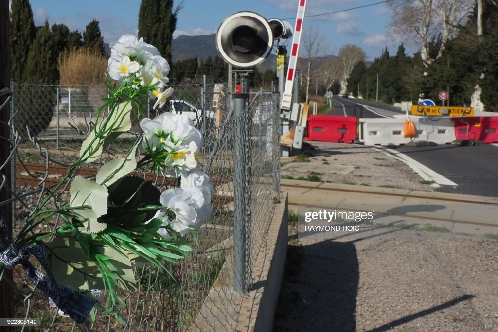 This general view shows flowers at a level crossing in Millas in southern France on February 21, 2018, where a schoolbus and a train collided in December 2017, killing six people. The driver of the school bus involved in the collision with a regional train in December in Millas (Pyrénées-Orientales) has on February 21, 2018, maintained his version of the 'barrier raised' during his hearing at Théza, near Perpignan, before the two judges of investigation in charge of the investigation into the accident that killed six, said his lawyer. /