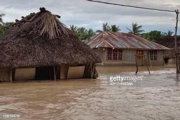 This general view shows homes surrounded by floodwaters in the village of Haitimuk in East Flores on April 4 after flash floods and landslides swept...