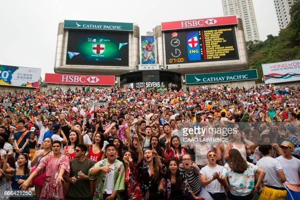 This general view shows people in the south stand singing during a match on the third day of the Hong Kong Rugby Sevens Tournament on April 9 2017 /...